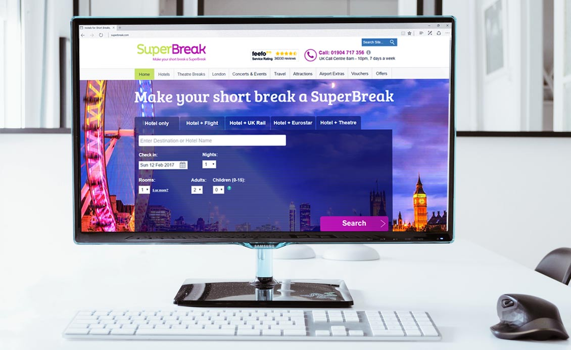 Photo of the SuperBreak homepage displayed on a monitor